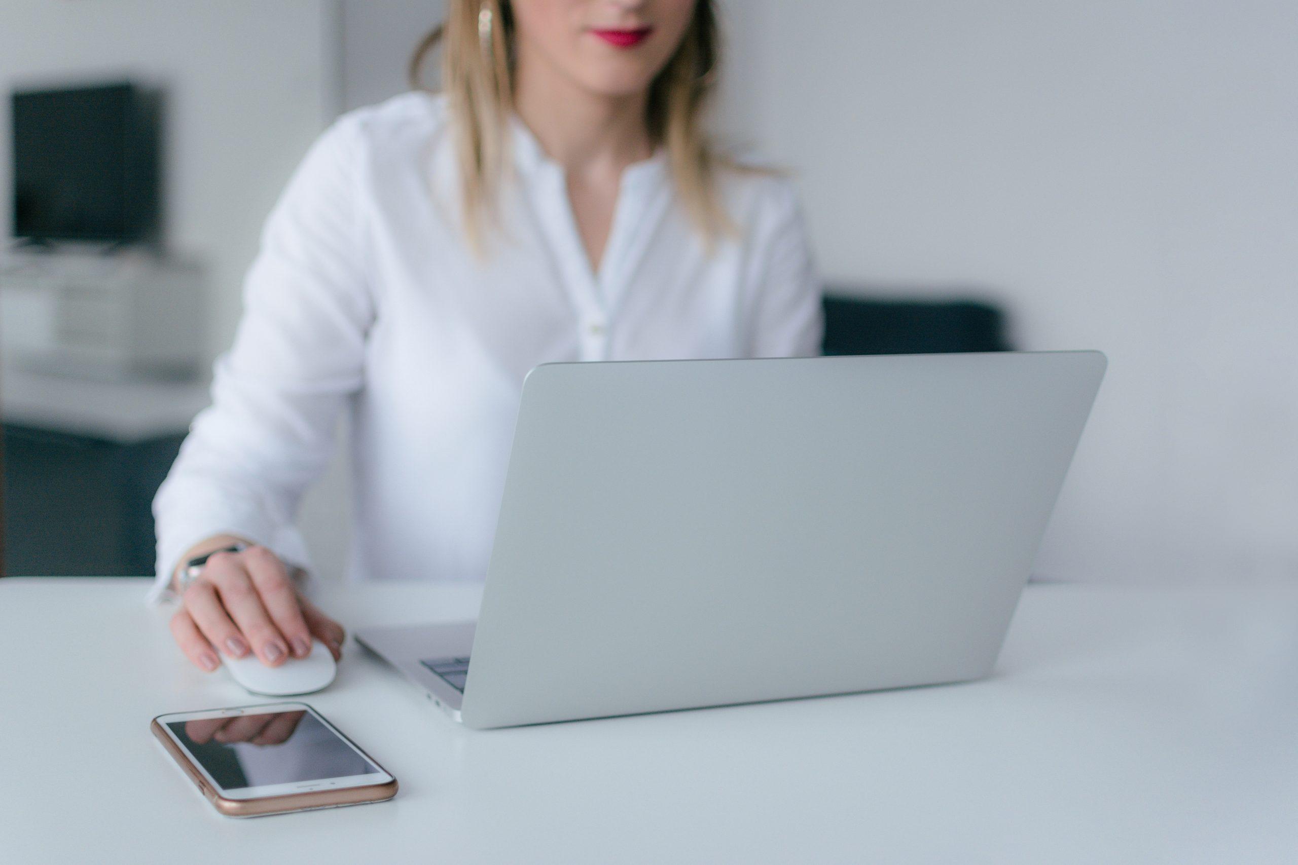 Gospodična, ki sedi pred prenosnim računalnikom v marketinški agenciji, s telefonom na mizi.